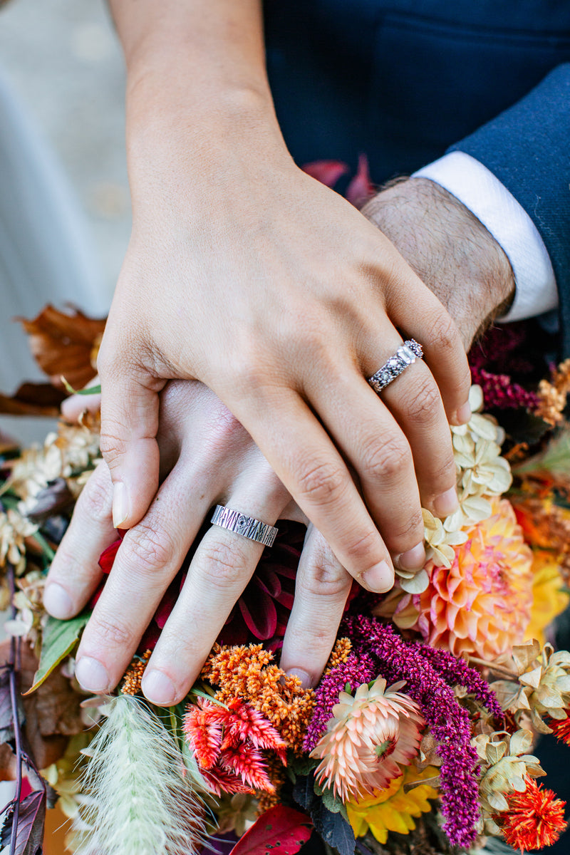 Hands being shown wearing the wedding bands. Their hands are on top of the wedding bouquet of local wildflowers that the rings were modeled after.