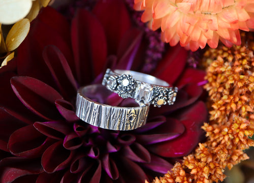 A matching set of engagement ring bands. One has a Herkimer diamond in the center and wildflowers on each side of the stone. The rings are placed upon a wildflower bouquet of flowers in oranges and reds.