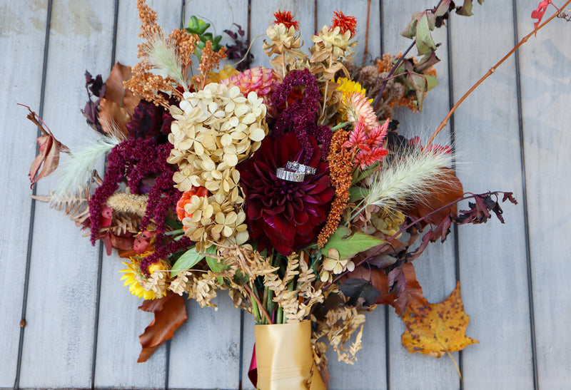 A beautiful local wildflower wedding bouquet with two wedding rings on top of the flowers. The flowers, vines, and dried grasses are in all different shades of tan, oranges, and reds.