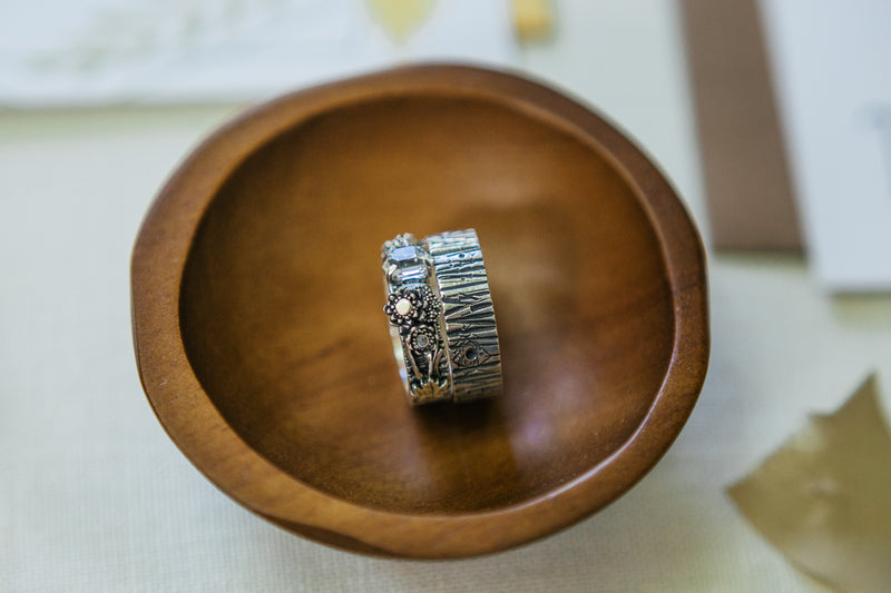 Two wedding rings in a wooden bowl. One ring shows the tree bark pattern and the other ring has a Herkimer diamond in the center of the band and tiny silver wildflowers next to it.