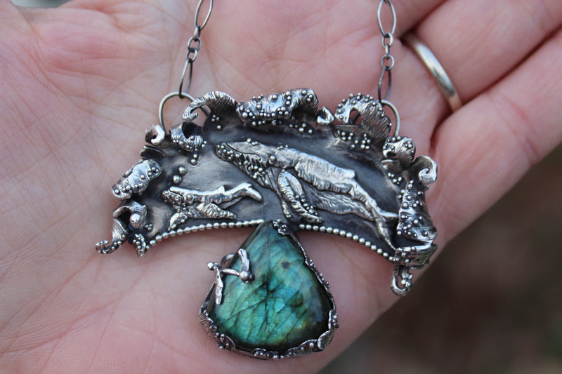 A hand holding the whale calf and mother pendant to show size.