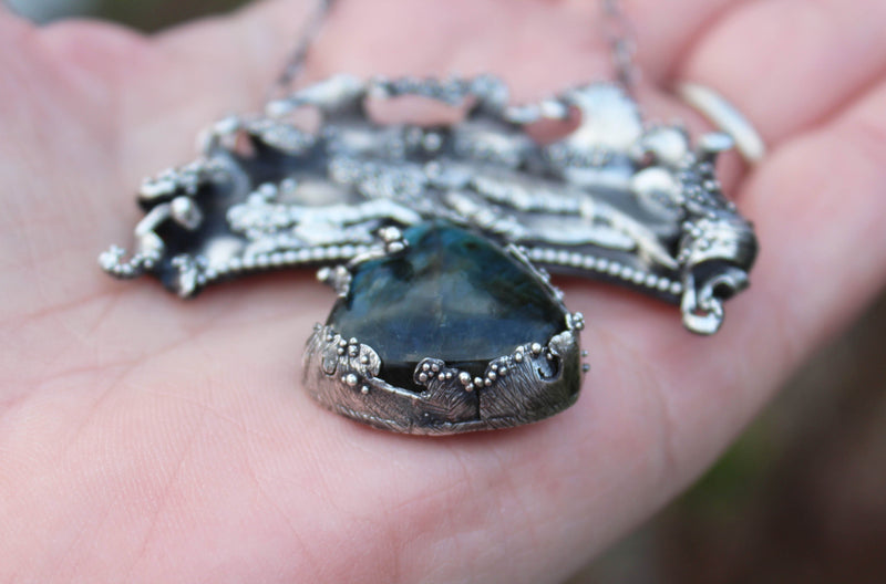 The side view of the ocean waves silver bezel that is holding the labradorite stone safely.