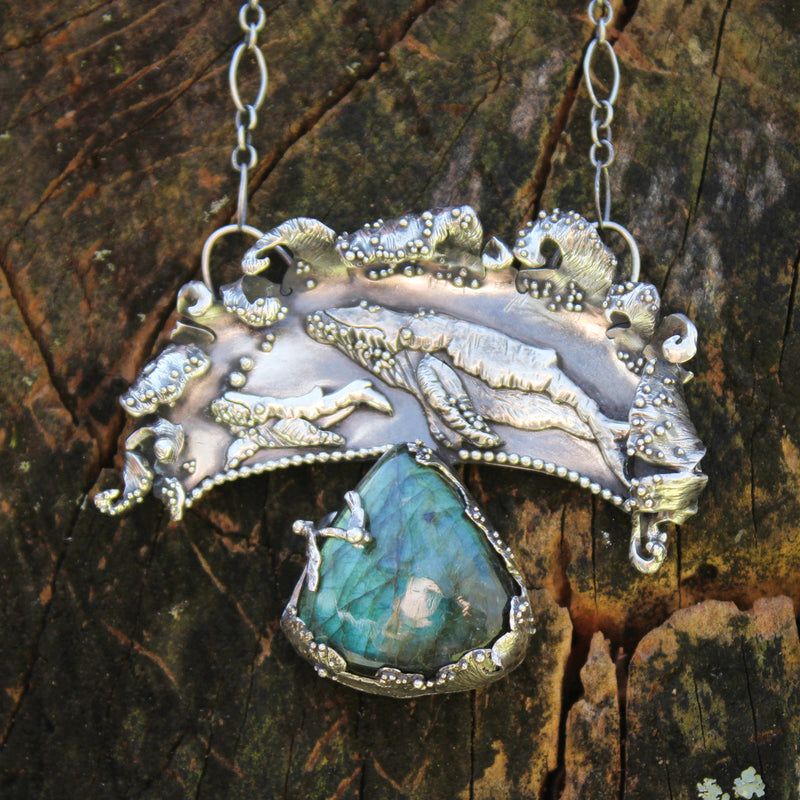 A one of a kind sterling silver whale and whale calf necklace. There is a triangular flashy blue labradorite stone at the bottom of the pendant and the stone is held safely with some wave patterned bezels. The baby whale has some bubbles coming up from him from where he is swimming and they are both under curled realistic looking ocean waves.