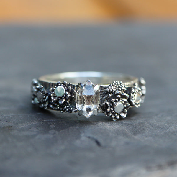 A close up of a handmade herkimer diamond ring with local silver wildflowers on each side of the diamond. It is shown on a dark grey piece of stone.