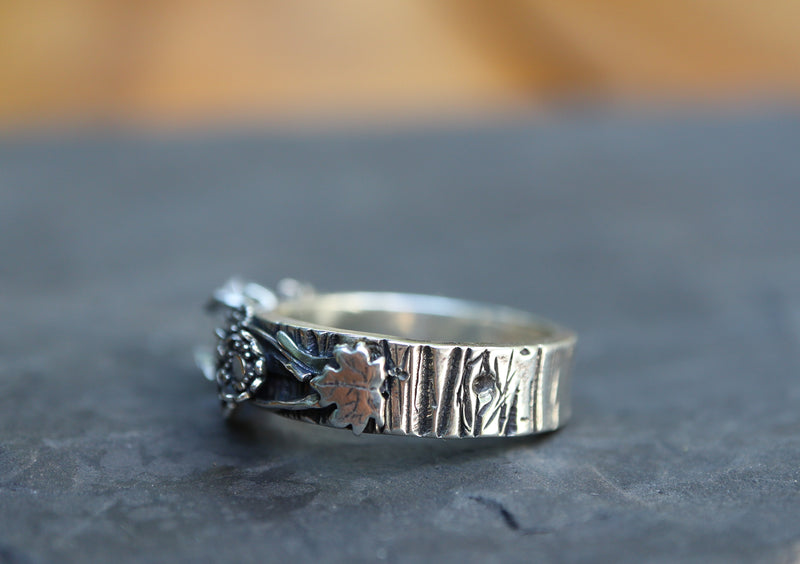 The side view of the ring showing the tiny maple leaf and the tree bark patterned band. It is shown on a dark grey piece of stone.