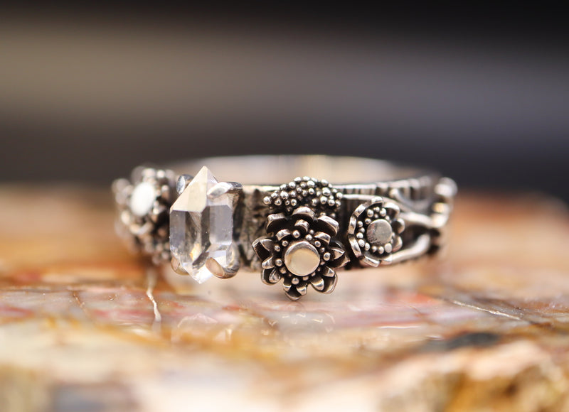 A Herkiner diamond and wildflower ring as a side view. This direction allows you to see the strawflowers, wheatheads, and the side of the diamond.