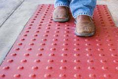 Person walking on red truncated domes