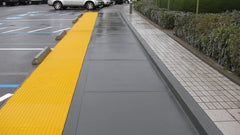 long line of yellow truncated domes between parking lot and sidewalk