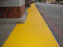 Long line of yellow truncated domes outside a store