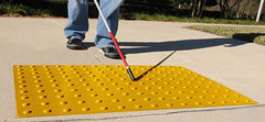 Blind person using cane on yellow truncated domes