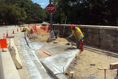 Workers installing cast-in-place style truncated domes in new concrete sidewalk curb