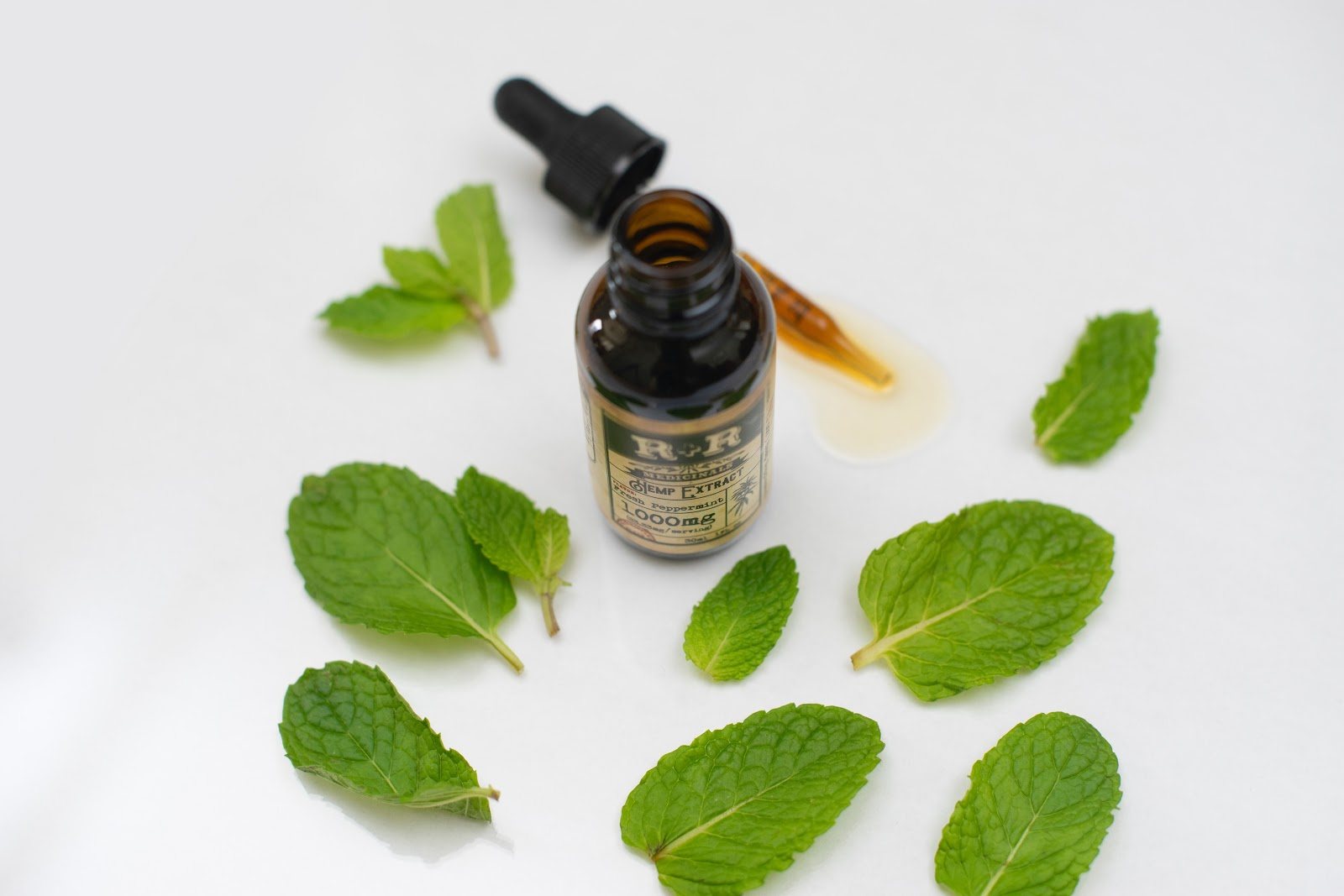 CBD oil surrounded by mint leaves