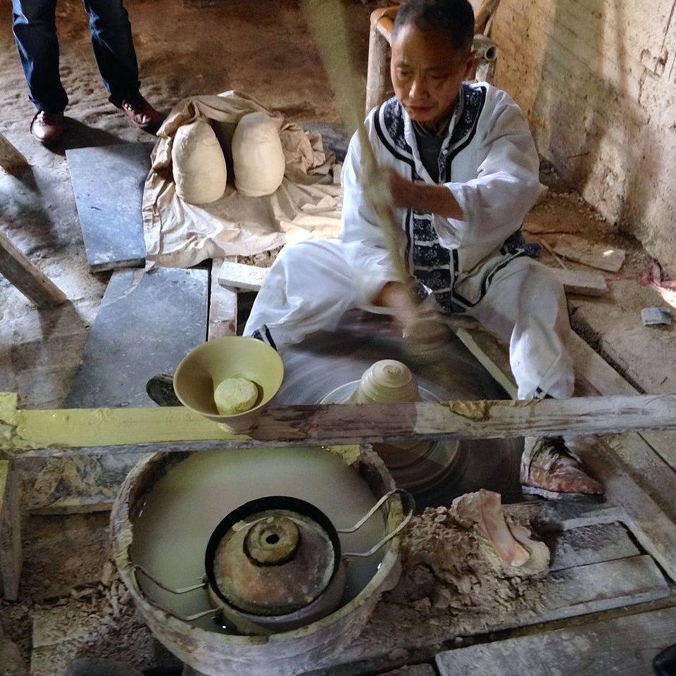 Potter spinning his pottery wheel to get momentum for more shaping of the piece his is making