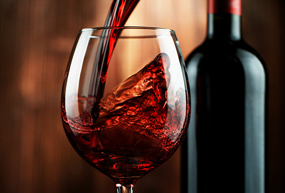 Wine glass being filled with red wine