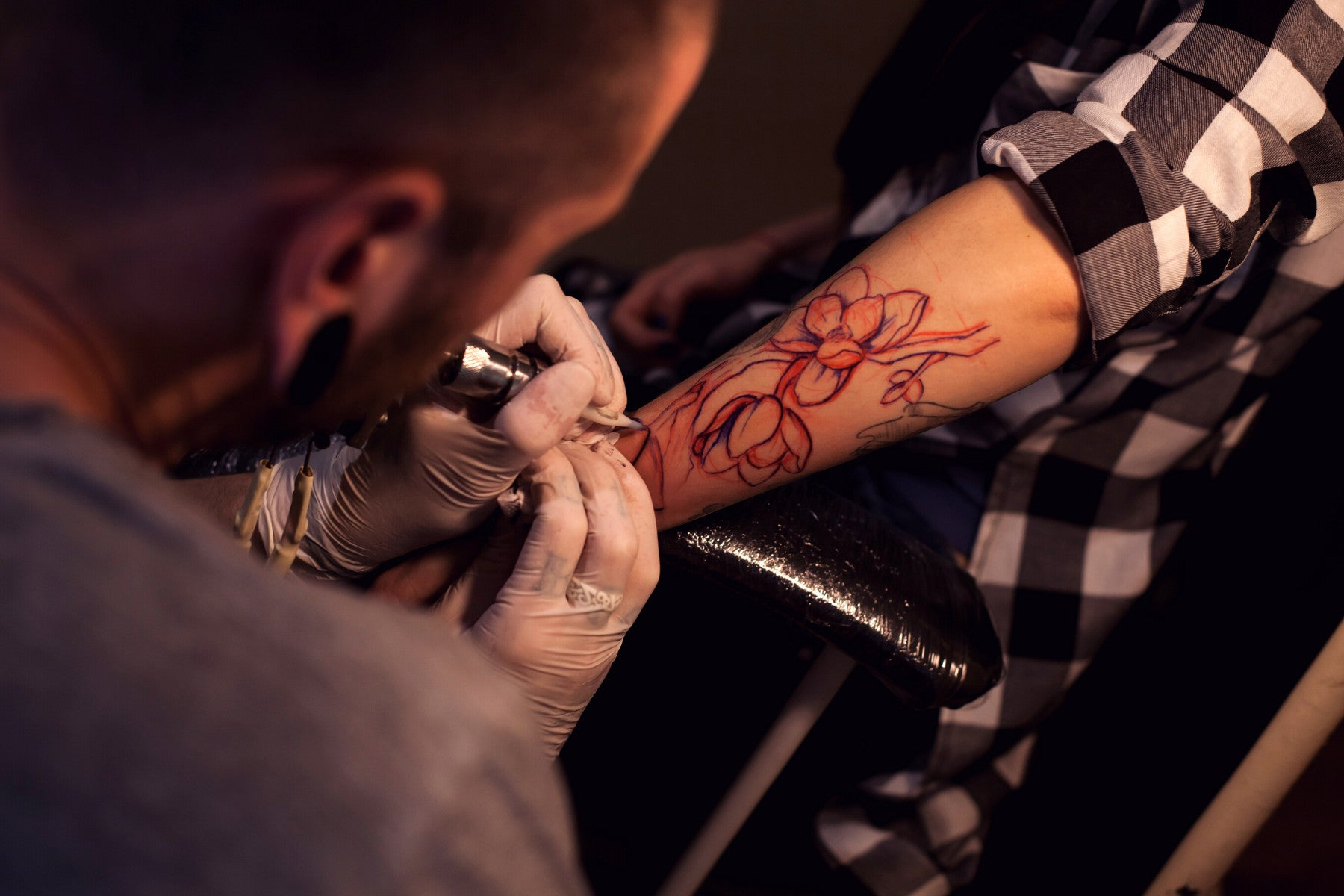 Male tattoo artist tattooing a large flower tattoo on a persons forearm