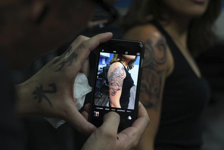 Person using a mobile device to take a picture of a tattoo on a girls arm