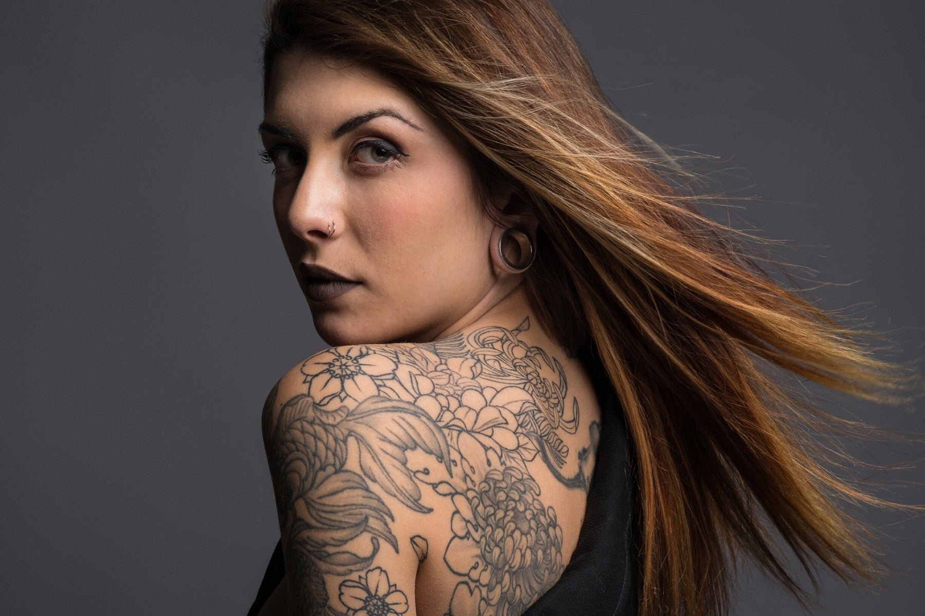 Attractive brunette girl with a full back and shoulder floral design black tattoos