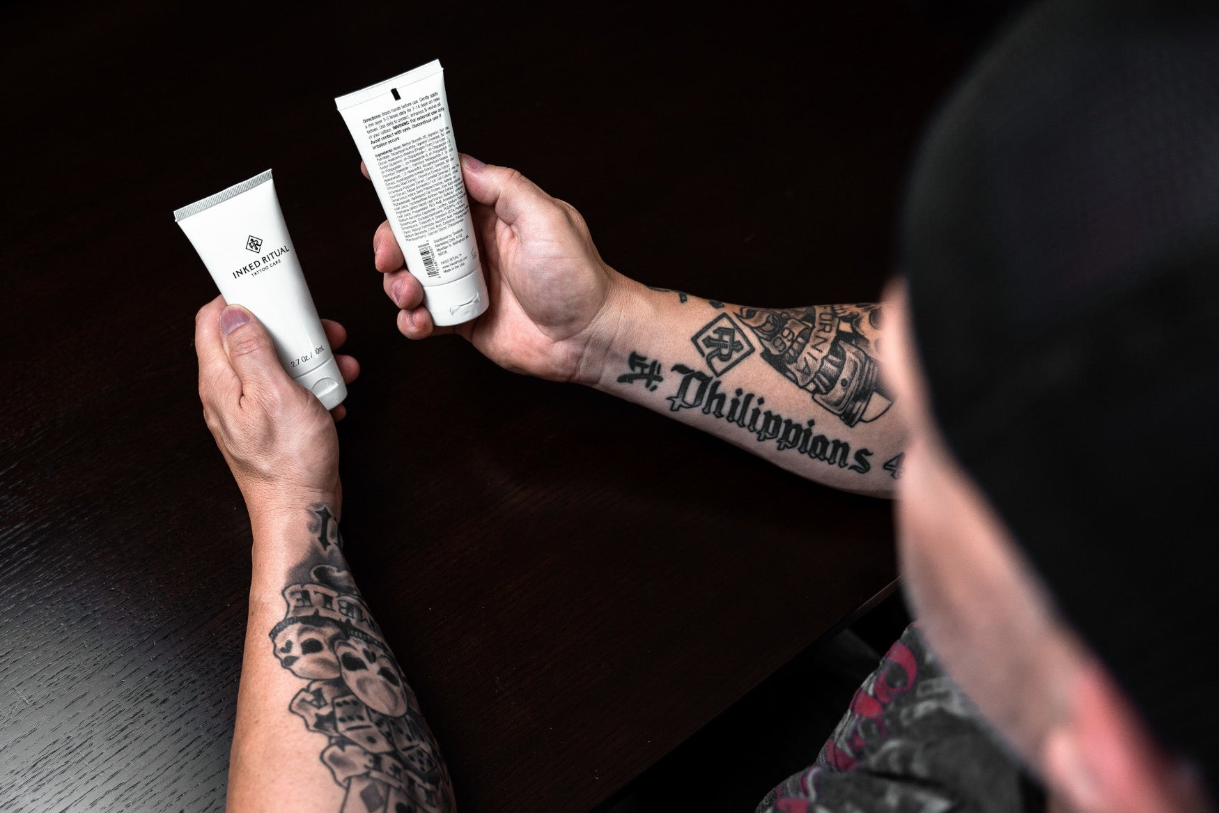Man with Tattooed Forearms Holding two Inked Ritual Tattoo Care Serum Philippians 4:13 Tattoo