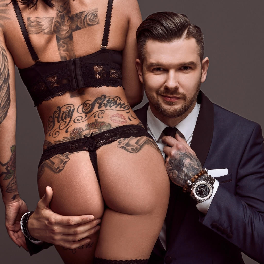 Attractive Tattooed Man In Suit With Hand On Sexy Female Tattoo Model With Back Tattoos And Black Lingerie