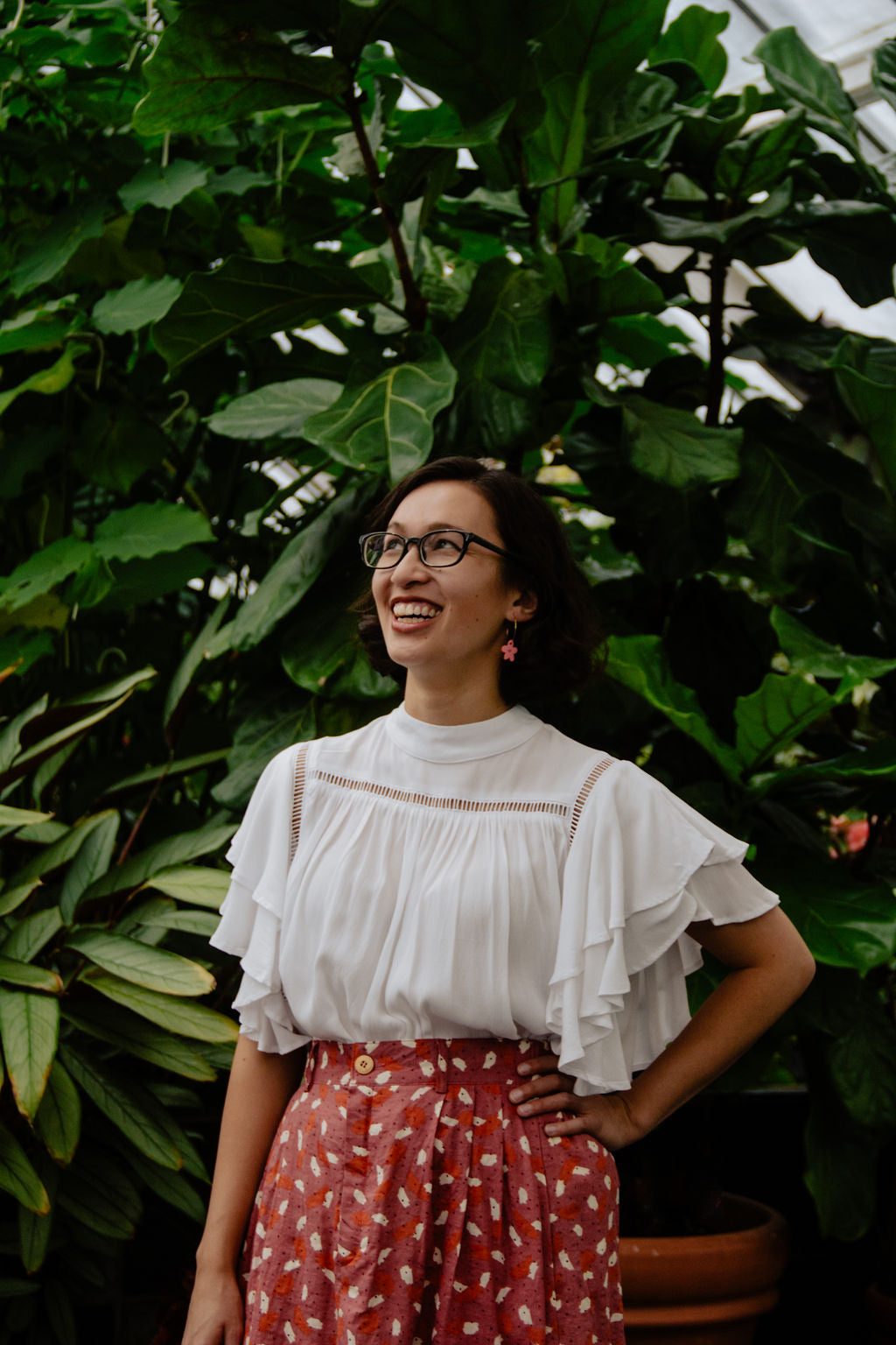 Cass amongst foliage in a green house. She is smiling with a hand on her hip, and looking away from the camera. She is wearing a floaty elbow length top, and a confetti patterned red/pink skirt.