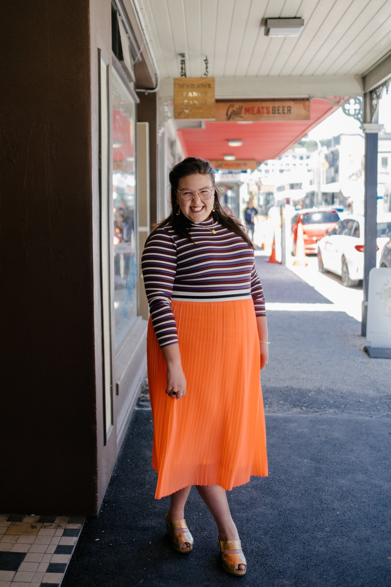 Sasha stands, smiling on Cuba Street, with the road stretching out behind her.
