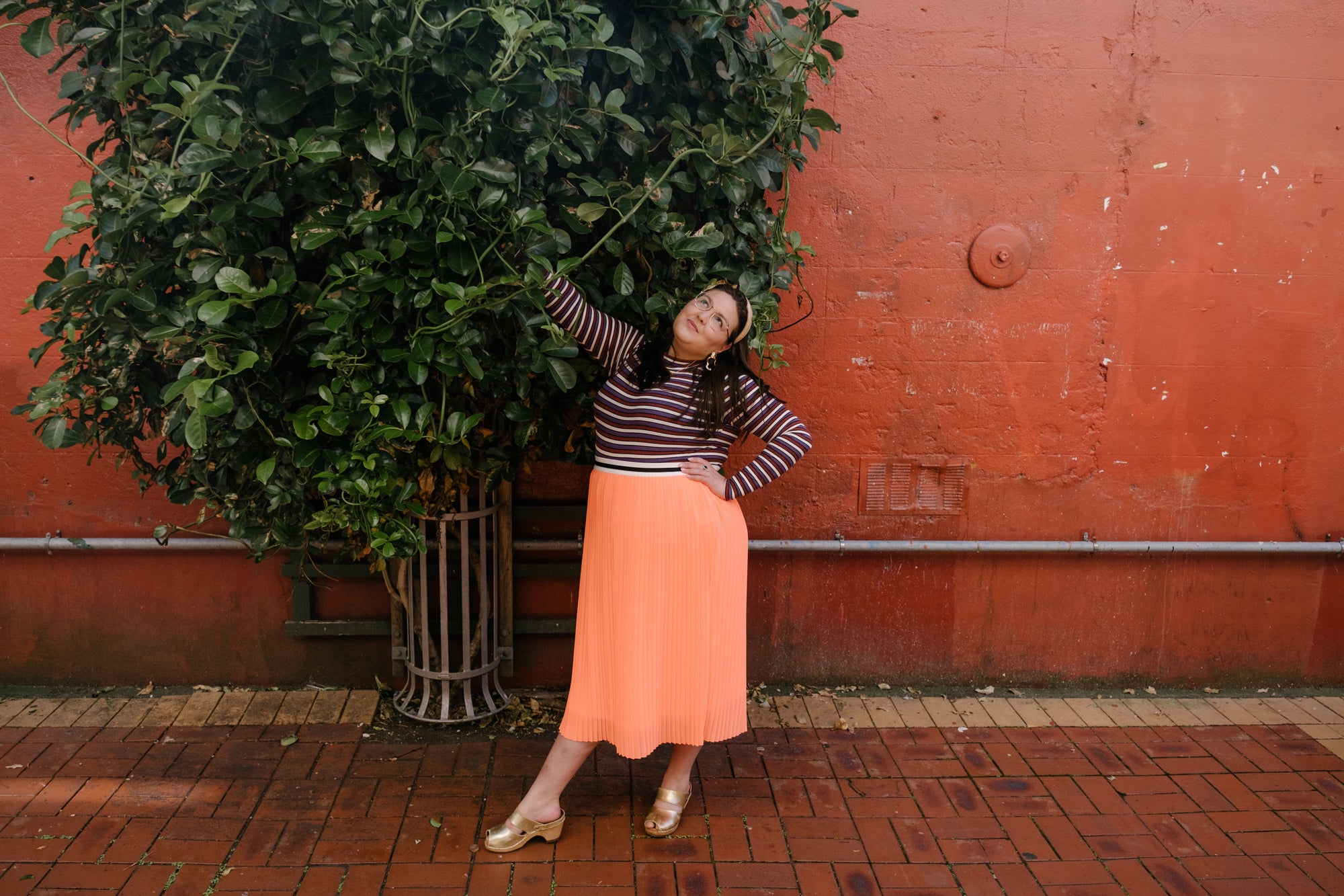 Sasha stands against a ochre wall with a vine growing up it. She has one arm reaching to the sky, and looks fabulous.