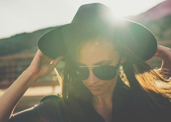 A women wearing sunglasses with a dark wide brim hat