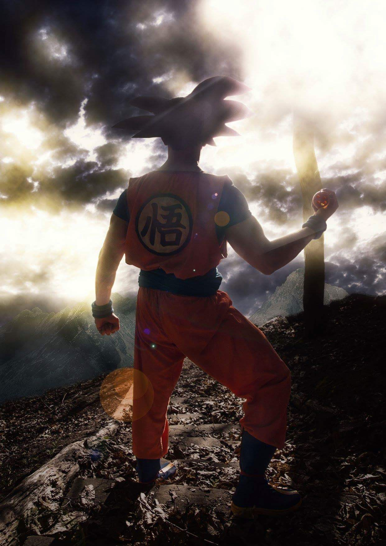 Son Goku from Dragon Ball Z Super Cosplay holding a dragonball whilst viewing the horizon