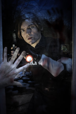 Leon S. Kennedy Resident Evil 2 Remake cosplay looking out of the window as a zombie looms in