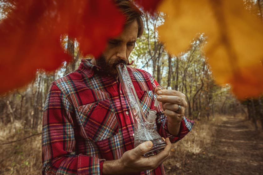 Man smoking from a glass bong in a forest