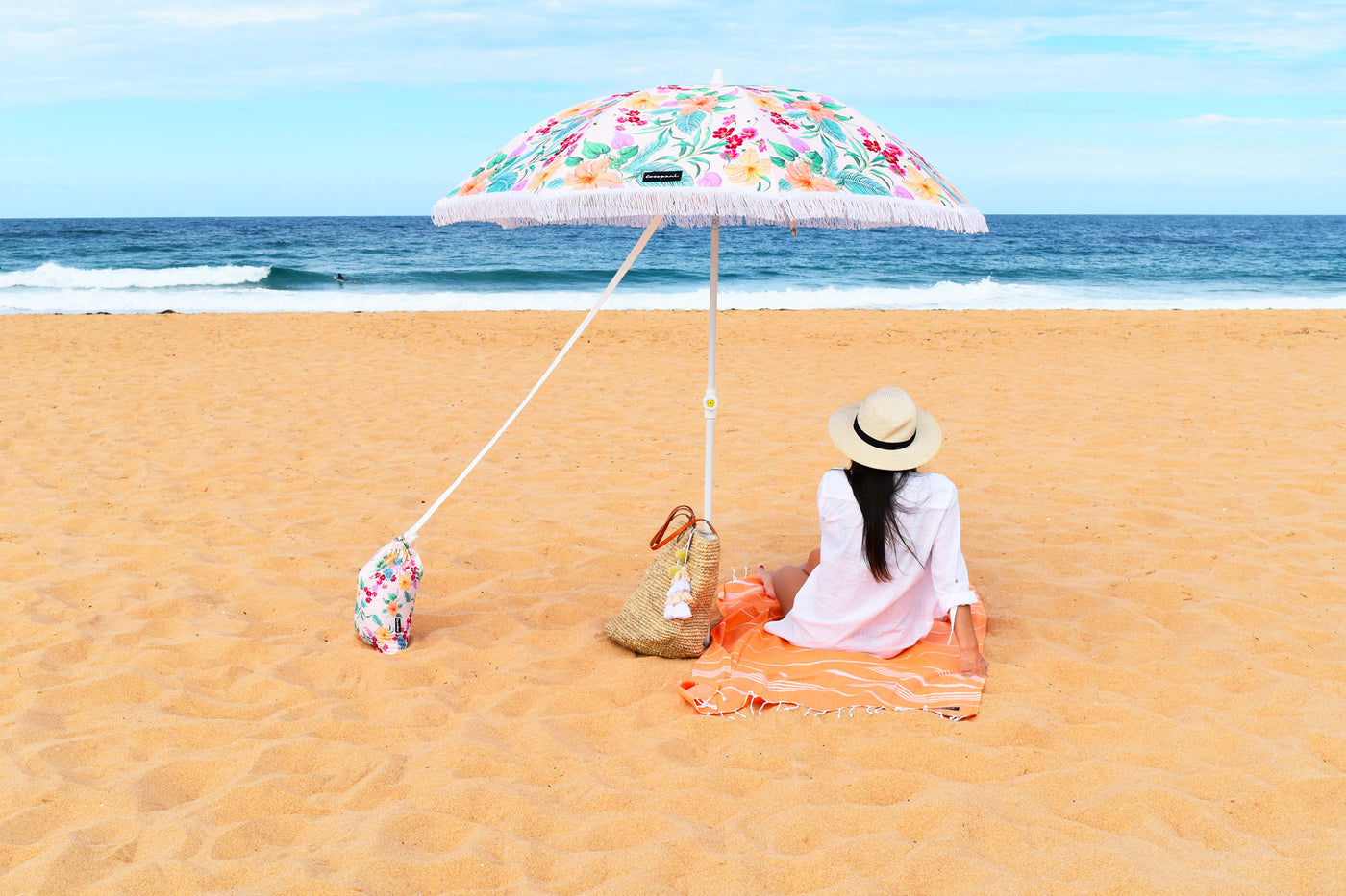 Girl under Cocopani umbrella looking at the ocean