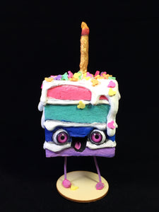 Rainbow Spun Cotton Cake figurine with white frosting