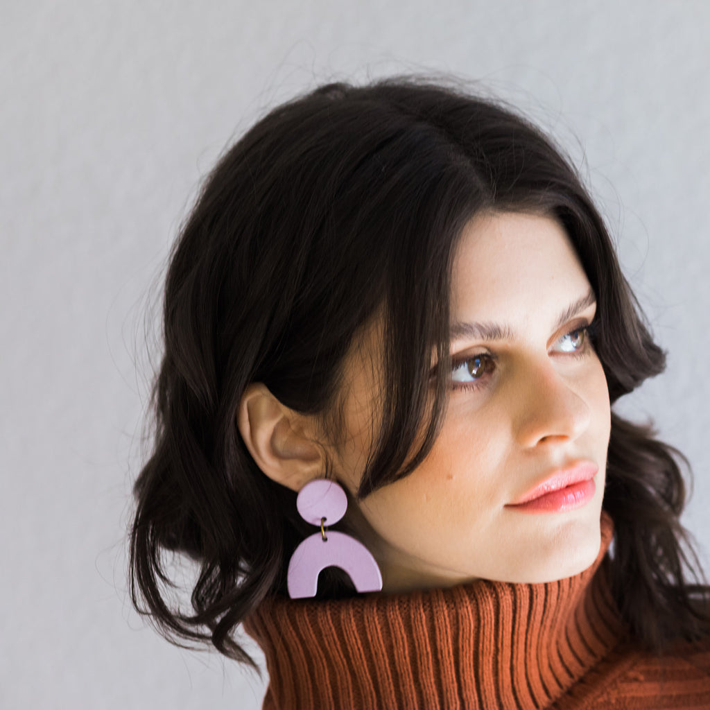 Lavender handmade ceramic statement earrings on model.