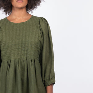 Olive green garment dyed quilted linen dress with bracelet length puffed sleeves.