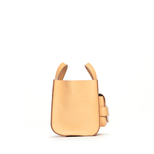 THE REGULAR light tan 'blonde' leather Pioneer Tote bag. Side front view showing large front pocket and grab handle in profile.