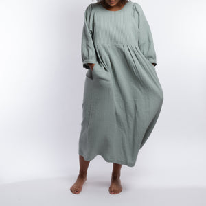 THE REGULAR Quilt Dress in eau de nil, light sage green cotton. Midi length, shown with puffed sleeves, quilted front bodice and belted at waist. Model wears with hands in large side pockets.