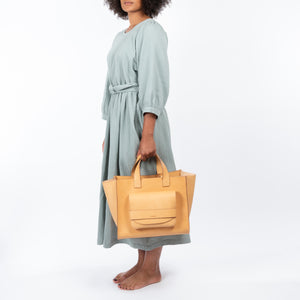 THE REGULAR blonde leather Pioneer Tote bag worn with eau de nil green Quilt Dress.