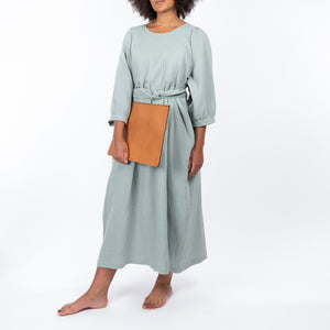 THE REGULAR Quilt Dress in eau de nil, light sage green cotton. Midi length, shown with puffed sleeves, quilted front bodice and belted at waist. Model wears with tan leather Folio clutch bag.