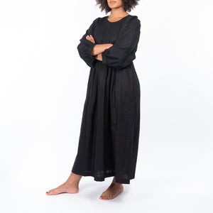 THE REGULAR Quilt Dress in black linen. Front view shows midi length, puffed sleeves, quilted bodice and unbelted at waist.