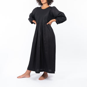 THE REGULAR Quilt Dress in black linen. Front view shows midi length, puffed sleeves, quilted bodice and unbelted at waist.  Model stands with both hands on hip.