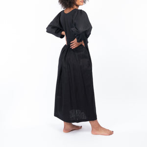 THE REGULAR Quilt Dress in black linen. Side, back view shows midi length, puffed sleeves, quilted bodice and belted at waist.