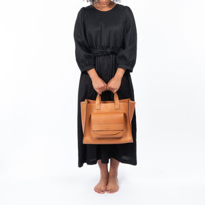 THE REGULAR Quilt Dress in black linen. Front view shows midi length, puffed sleeves, quilted bodice and belted at waist.  Model carries large tan leather Pioneer Tote bag.