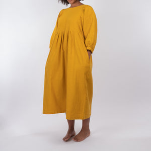 THE REGULAR Quilt Dress in mustard yellow, garment dyed linen. Midi length, shown with puffed sleeves, quilted front bodice and unbelted at waist.