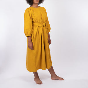THE REGULAR Quilt Dress in mustard yellow, garment dyed linen. Midi length, shown with puffed sleeves, quilted front bodice and belted at waist.