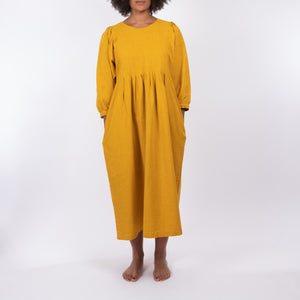 THE REGULAR Quilt Dress in mustard yellow, garment dyed linen. Midi length, shown with puffed sleeves, quilted front bodice and unbelted at waist. Model stands with hands in side pockets.