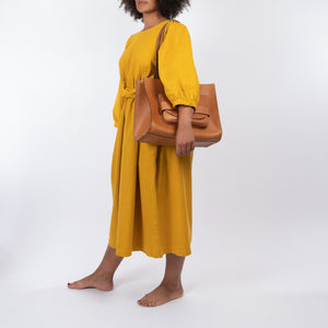 THE REGULAR Quilt Dress in mustard yellow, garment dyed linen. Midi length, shown with puffed sleeves, quilted front bodice and belted at waist. Model wearing large tan lether Pioneer Tote as a shoulder bag.