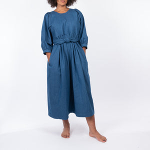 THE REGULAR Quilt Dress in regular wash denim. Front view shows midi length, puffed sleeves and belted at waist.  Shown being worn with hands in pocket.