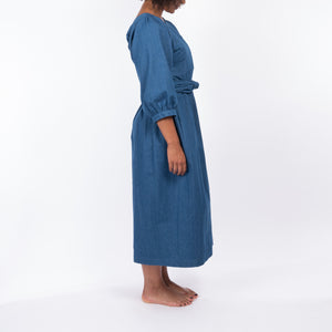 THE REGULAR Quilt Dress in regular wash denim. Side view shows midi length, puffed sleeves and belted at waist.