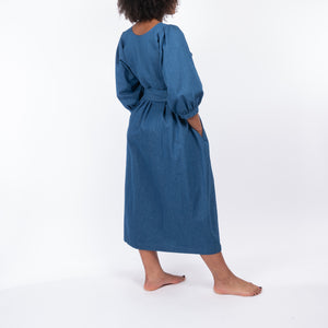 THE REGULAR Quilt Dress in regular wash denim. Back view shows midi length, puffed sleeves and belted at waist.  Shown being worn with hands in pocket.
