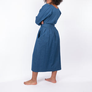 THE REGULAR Quilt Dress in regular wash denim. Side, back view shows midi length, puffed sleeves and belted at waist.